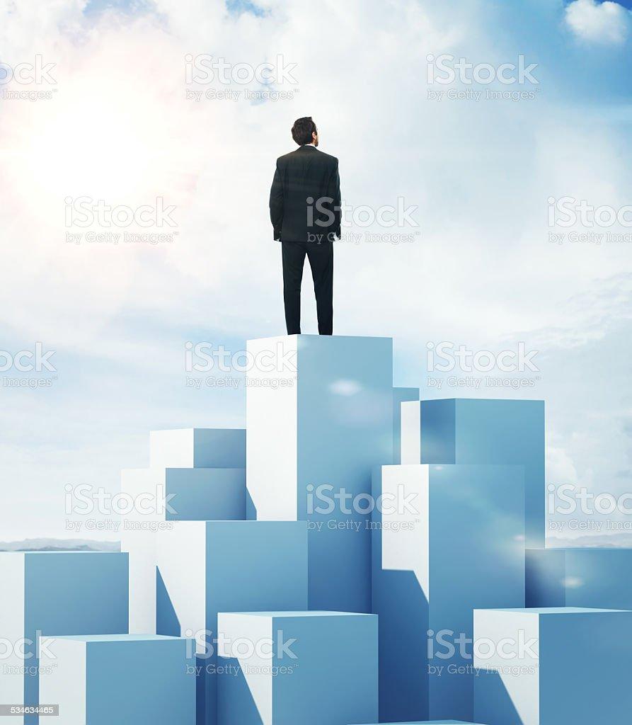 Man standing on highest cube stock photo