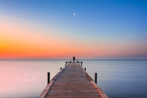 Man standing on jetty at beach with sunrise and moon