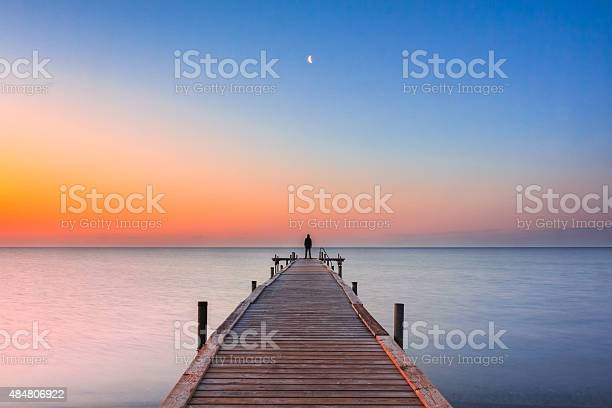 Photo of Man standing on jetty at beach with sunrise and moon