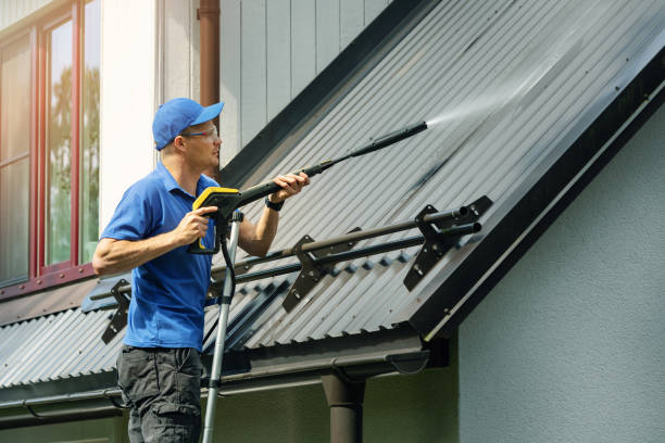 man standing on ladder and cleaning house metal roof with high pressure washer stock photo