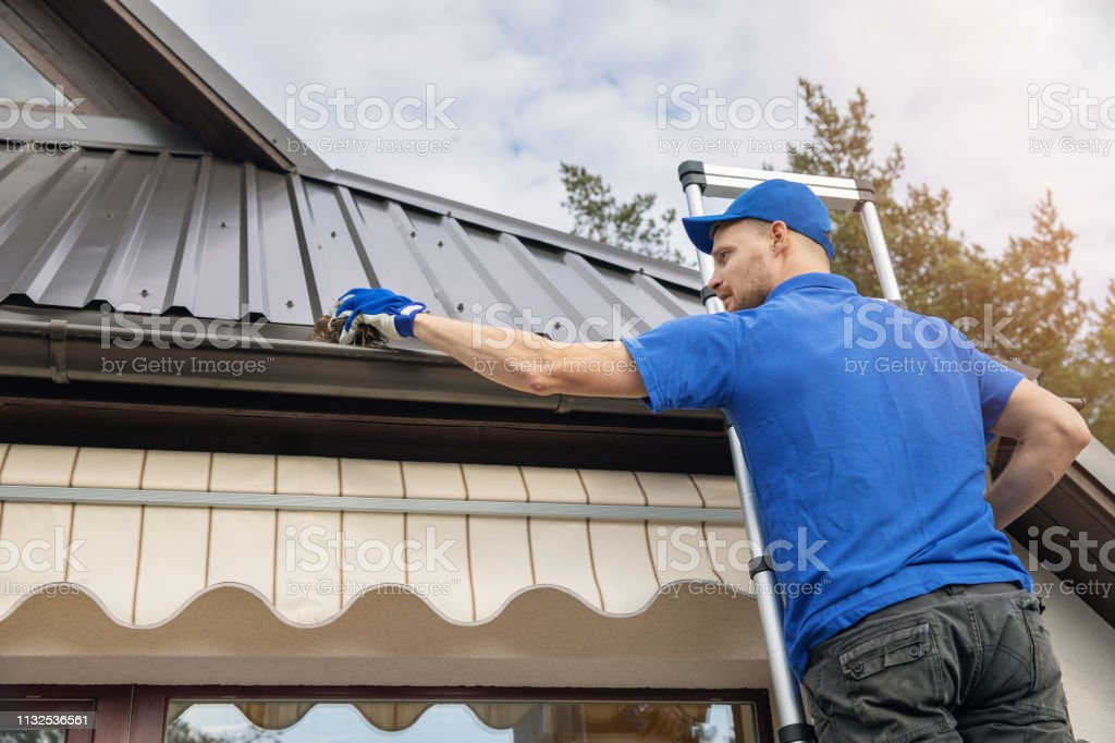 man standing on ladder and cleaning roof rain gutter from dirt stock photo
