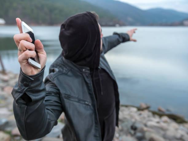 Homme debout sur la plage du lac et de jeter son téléphone intelligent dans l'eau - Photo