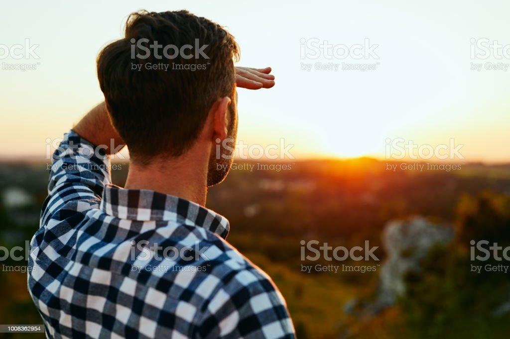 Man permanent op weide in bergen en de zonsondergang bewonderen - Royalty-free Aankomst Stockfoto