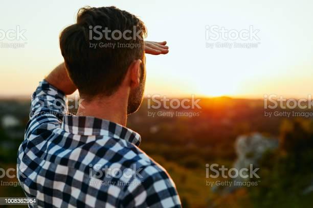 Man Permanent Op Weide In Bergen En De Zonsondergang Bewonderen Stockfoto en meer beelden van Aankomst