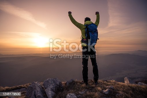 Rear view of man with arms raised standing on mountain against sky during sunset.