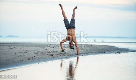 istock Man standing on one hand at beach. 904510536