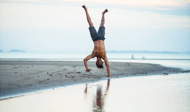 Man standing on one hand at beach. stock photo