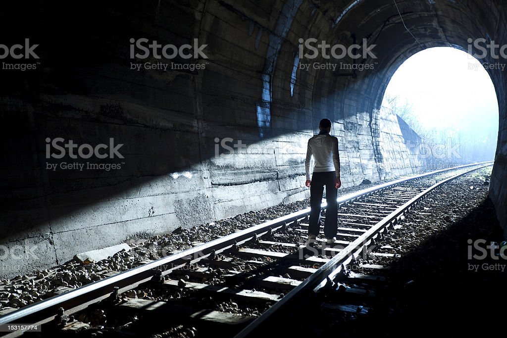 Man standing on railroad tracks, reaching end of the tunnel stock photo