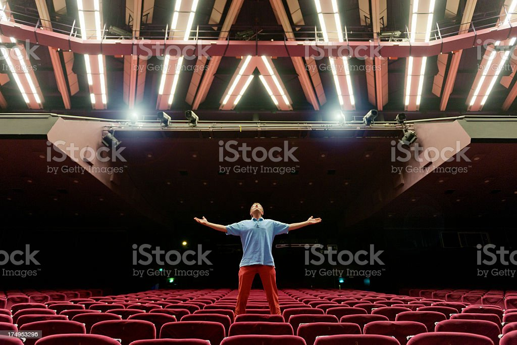 man standing with arms outstretched on red velvet seat looking up in...
