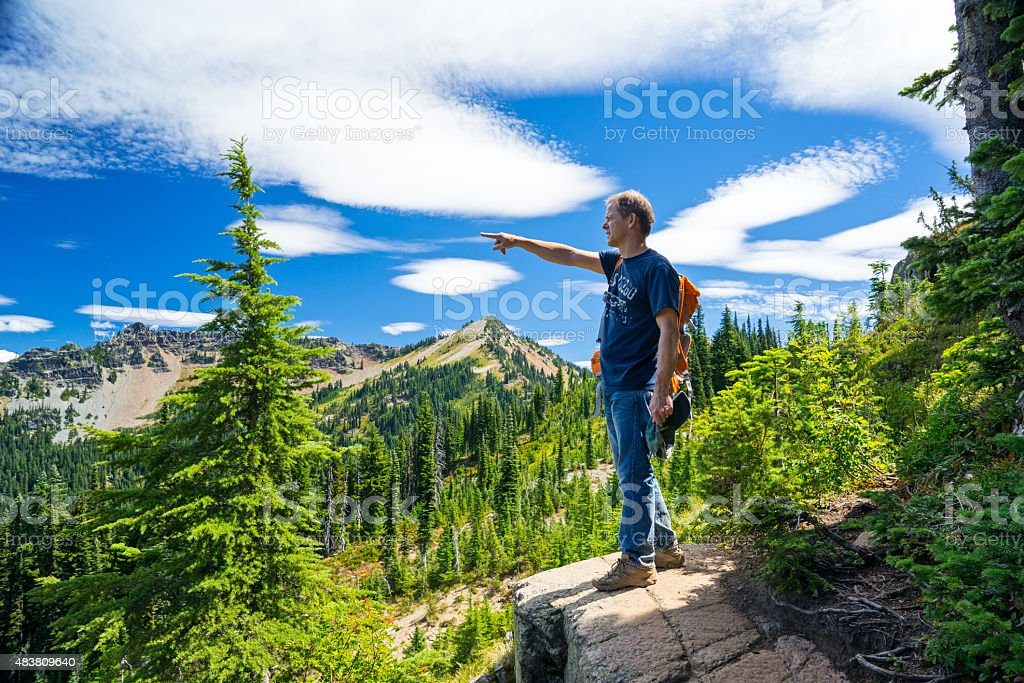 Man Standing on Rock and Pointing At Mountains stock photo
