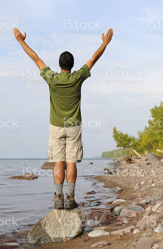 Man Standing on Rock at Shoreline With Arms In Air royalty-free stock photo