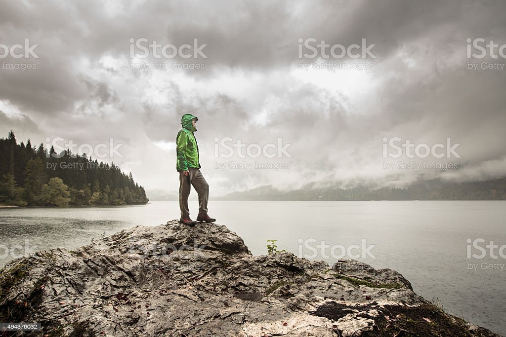 Man standing on rock beside a mountain lake in rain stock photo