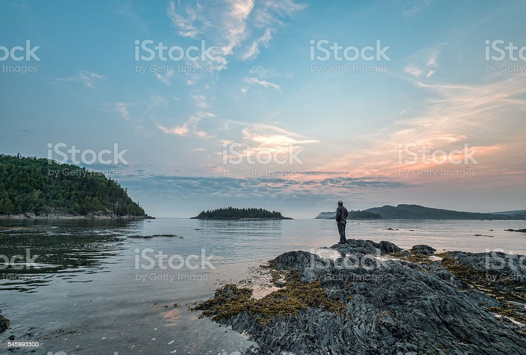 Man Standing on Rock Looking Out Over St. Lawrence River stock photo