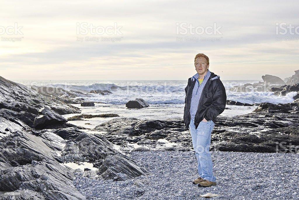 Man standing on rocky rugged coastline at Botanical Beach stock photo