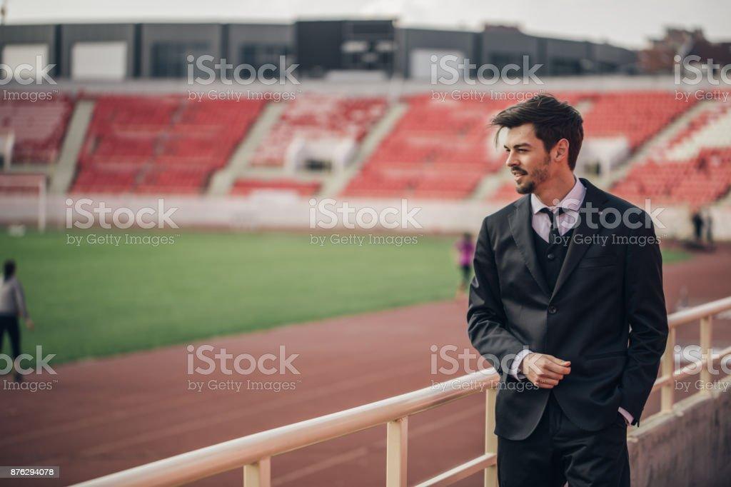 Man standing on stadium grandstand stock photo