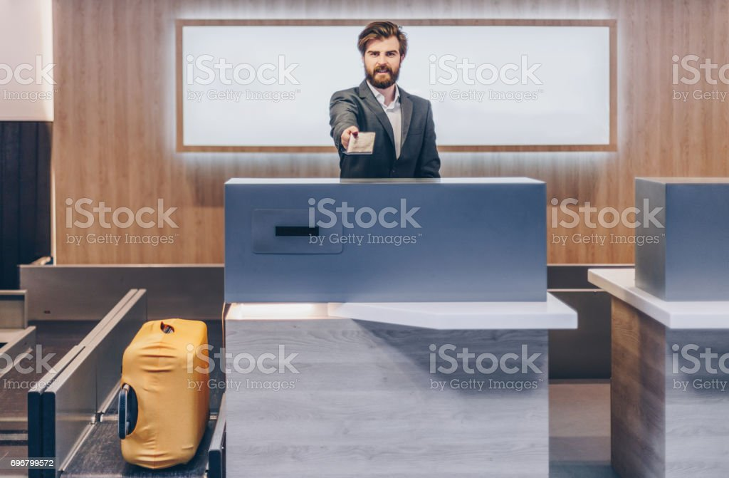Man standing on the airport check-in counter and giving pasport stock photo