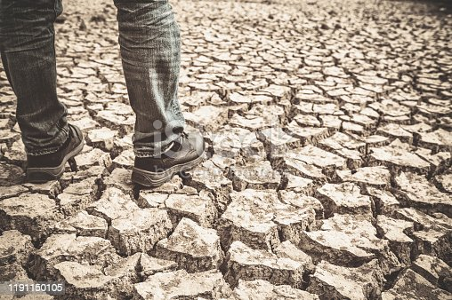 A man standing on the drought ground, part of body, only leg.