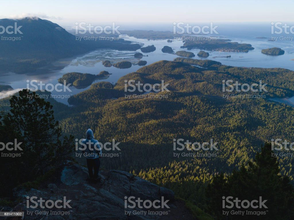 Man standing on the edge of cliff above bay stock photo