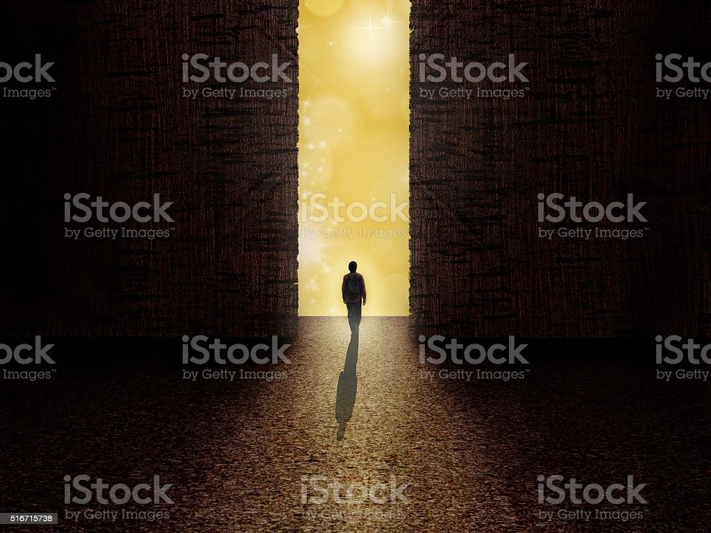 Man standing on the edge of darkness and light stock photo