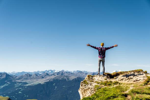 손을 들고 바위 가장자리에 서 있는 남자. 세세다 근처 이탈리아 알프스. - mountain top 뉴스 사진 이미지