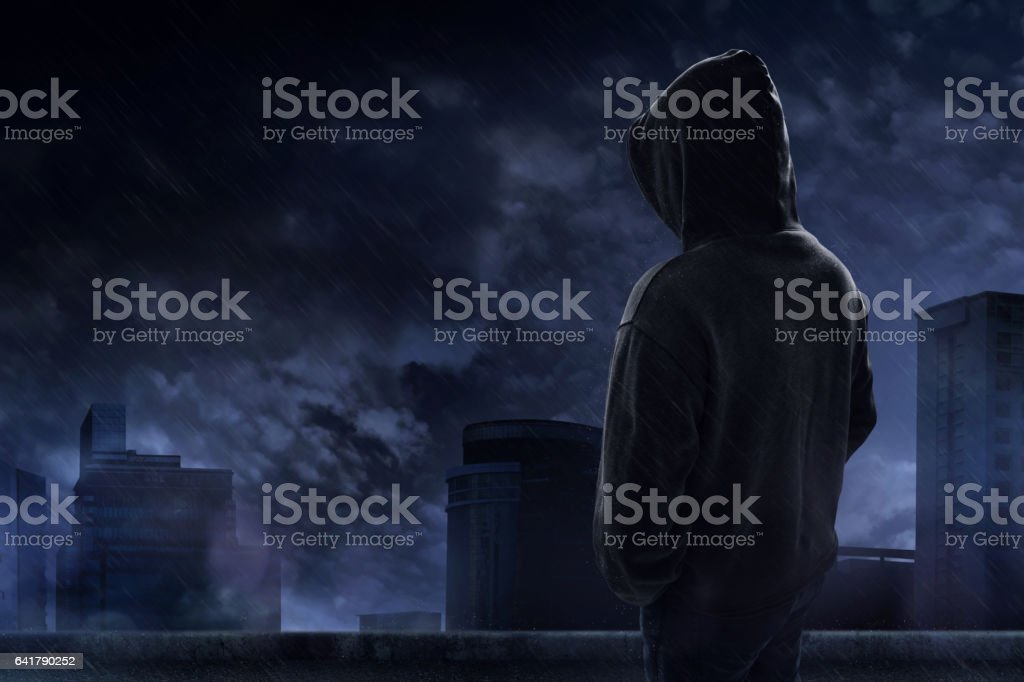 Man standing on the rooftop in a rainy night stock photo