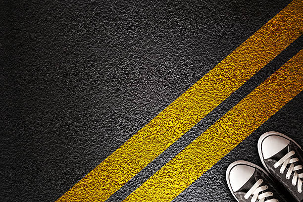 Man Standing on the yellow line Yellow line on the asphalt boundary stock pictures, royalty-free photos & images