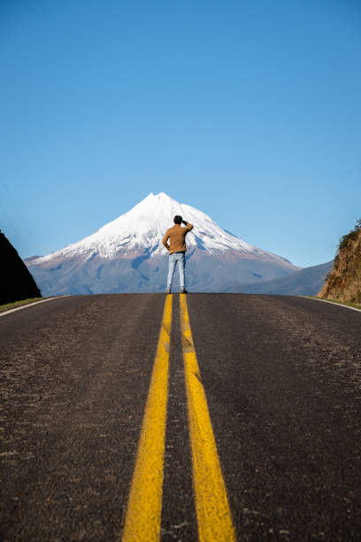 Man standing on top of road overlooking top of mount taranki peak in New Zealand stock photo