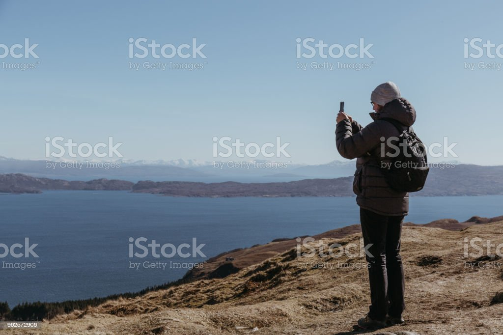 Man standing on top of the Old Man of Storr walk on Isle of Skye, taking photos on his mobile phone. stock photo