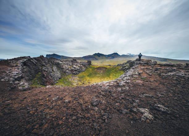Homme debout au sommet du cratère volcanique - Photo