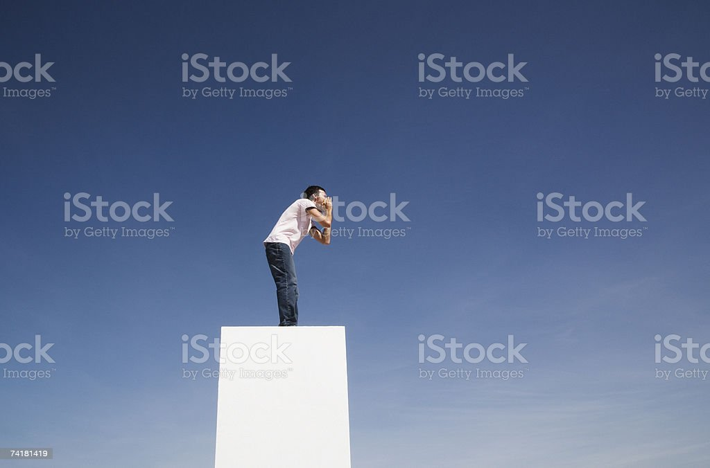 Man standing on wall outdoors shouting royalty-free stock photo