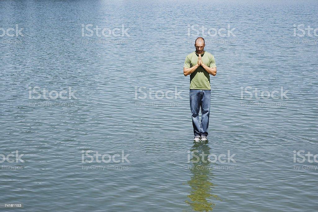 Homem de pé na água Rezar foto de stock royalty-free