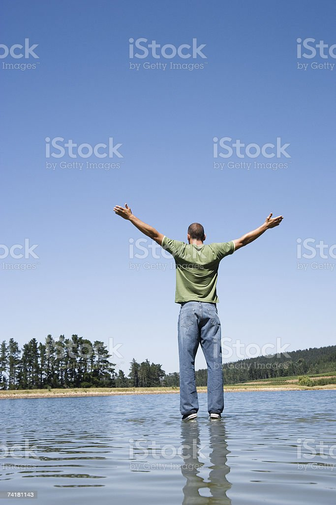 Man standing on water with arms up royalty-free stock photo