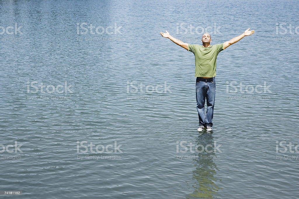 Homem de pé na água com os braços para cima foto de stock royalty-free