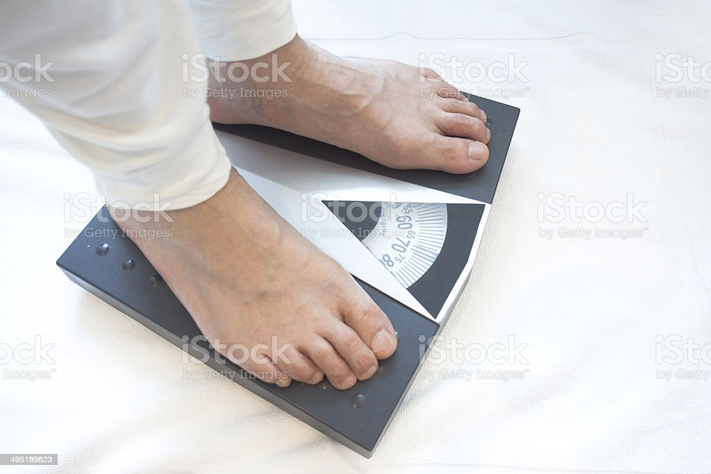 Man standing on weight scales stock photo