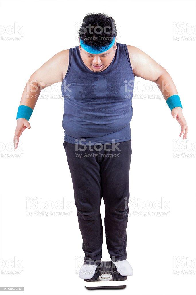 Man standing on weight scales stok fotoğrafı