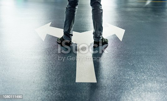 istock Man standing on white direction arrow 1080111490