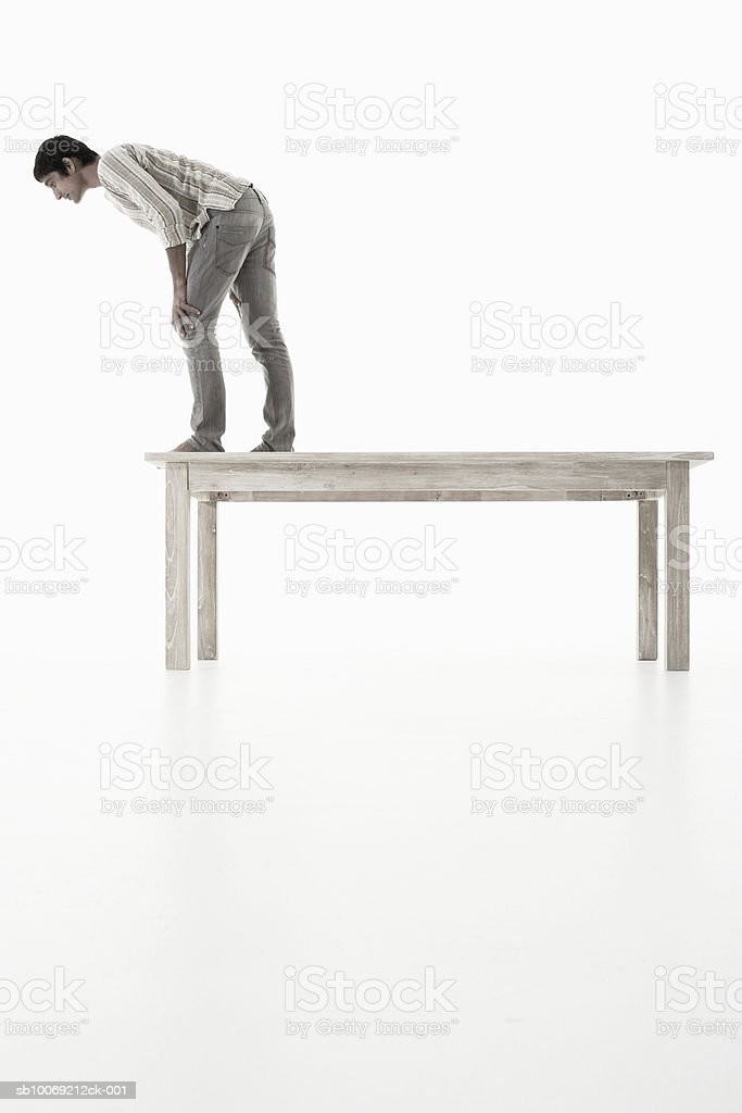 Homme debout sur une table en bois regardant vers le bas sur blanc backgrou photo libre de droits