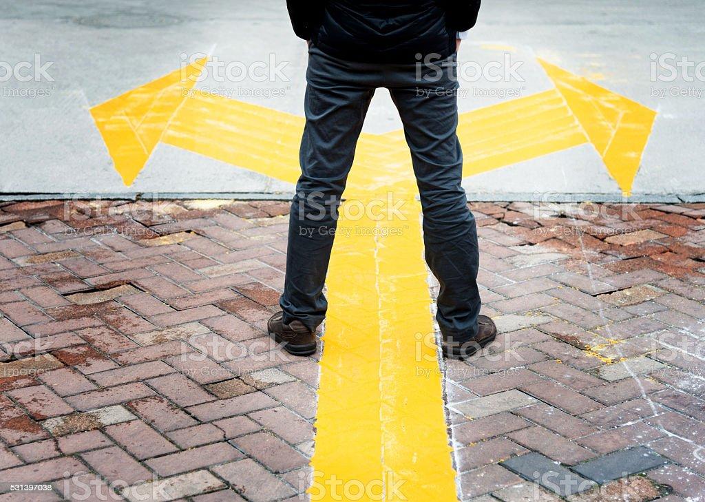 Man standing on yellow direction arrow stock photo