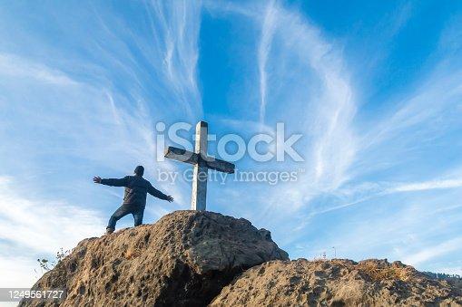 istock Man standing open arms near a cross on a cliff in Uttarakhand 1249561727
