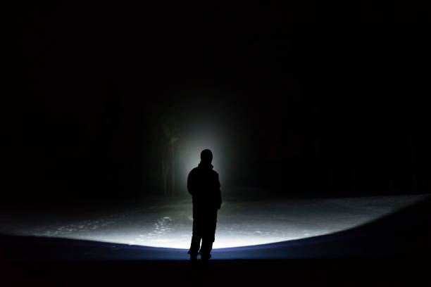 Homem de pé ao ar livre à noite na floresta, brilhando para a frente com lanterna - foto de acervo
