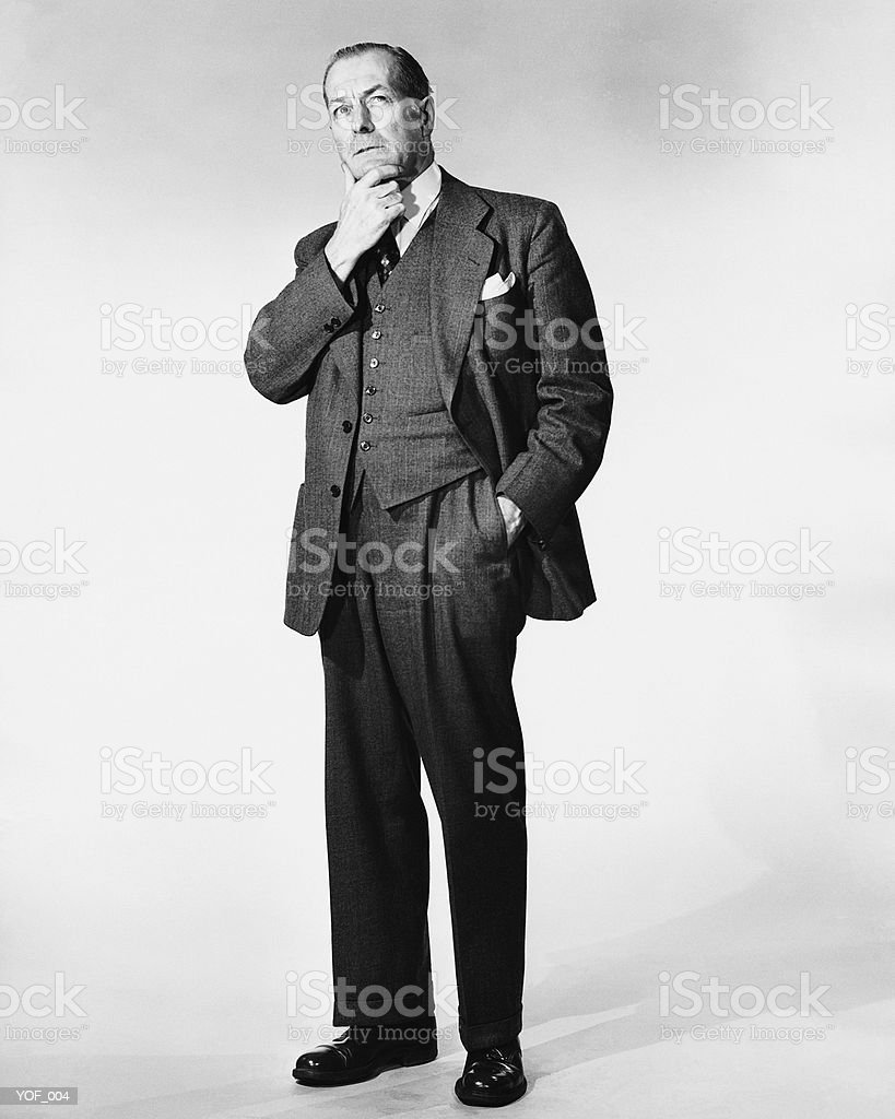 Man standing, rubbing chin royalty free stockfoto