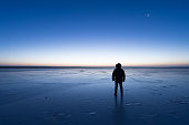 Man standing the frozen lake at dawn