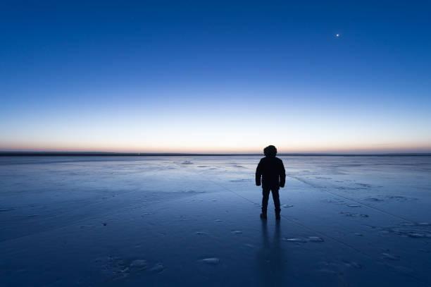 Mann, der den zugefrorenen See in der Dämmerung – Foto