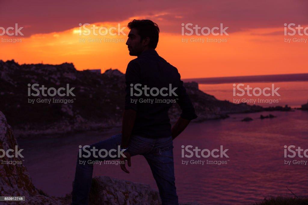 man standing thinking back light sunset lighting side view profile...
