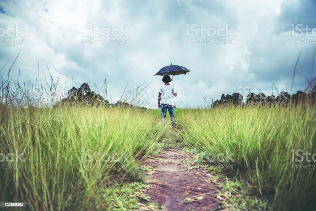 man standing umbrella On the green meadow in the rainy season. Asian man stock photo