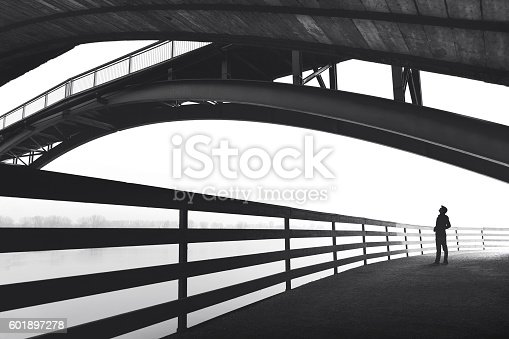 istock Man standing under bridge arch 601897278