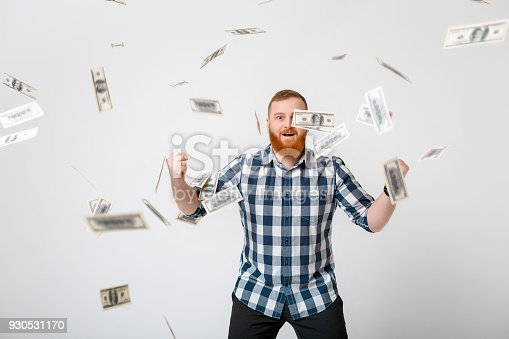 969671638istockphoto man standing under money rain 930531170