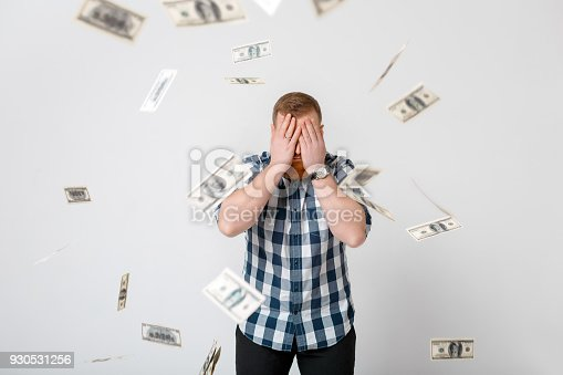 969671638istockphoto man standing under money rain 930531256