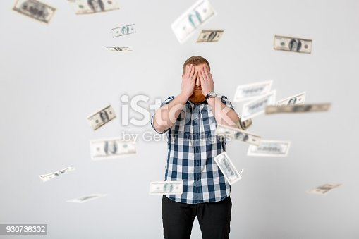 969671638istockphoto man standing under money rain 930736302