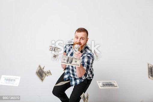 969671638 istock photo man standing under money rain 930736370